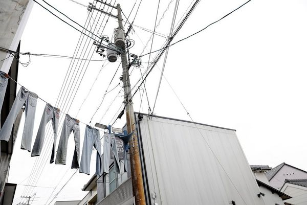 In a film still from Made in Japan, jeans hang across the entrance to Jeans Street, in the Okayama prefecture of Japan.