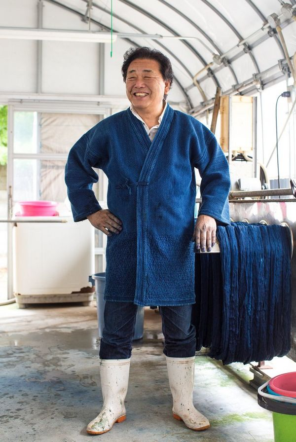 In a film still from Made in Japan, a smiling denim factory worker wears a blue denim robe, denim jeans and white boots.