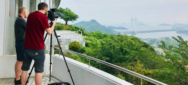 Made in Japan filmmakers Jack Flynn and Nick David stand on a balcony filming a distant bridge.