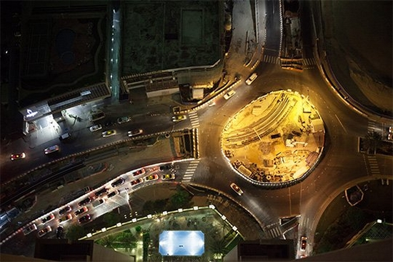 An overhead view of a busy road junction at night, photographed by Olivia Arthur.