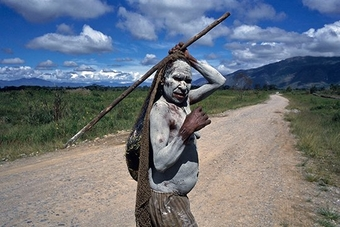 An indigenous tribeswoman in Papua covered in white mud. Photo by Susan Meiselas.