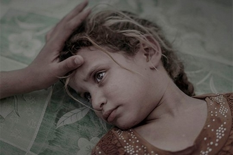 A blonde five-year-old girl lies on a green printed mattress, a hand stroking her hair