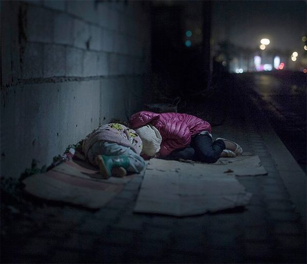 Two small children lie on flattened cardboard boxes by a wall in a dark, quiet street, wearing pink coats