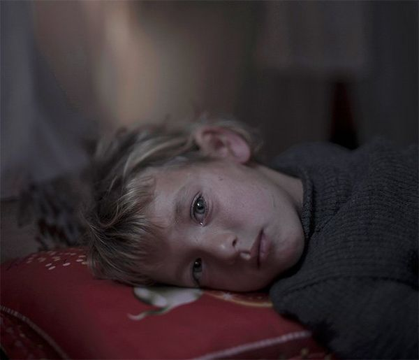 A blonde child lies with her head on a red pillow, looking at the camera