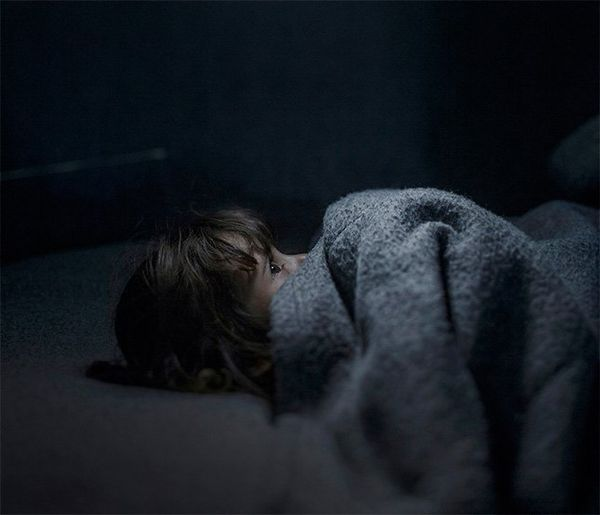 A small child lies on a grey bed under a grey wooden blanket that they have pulled up to cover most of their face. Their eyes are wide open, looking straight up at the ceiling