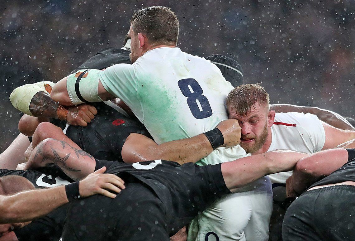 England and New Zealand rugby players in a ruck, photographed by Marc Aspland.