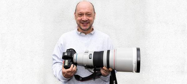 Sports photographer Marc Aspland holds a Canon camera and telephoto lens.