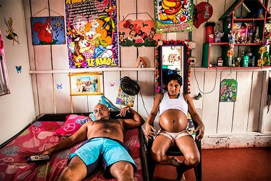 A heavily pregnant woman sits on a chair next to a man lying on a bed, her top rolled up to expose her stomach. They are in a brightly-lit room decorated with colourful posters and a shelf unit holding cosmetics bottles and small stuffed toys.