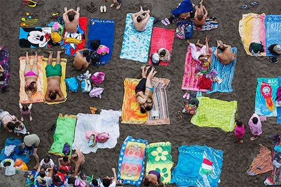 An overhead shot of people sunbathing on colourful towels at a black sand beach. Taken by Martin Parr on a Canon EF 70-300mm f/4.5-5.6L IS USM lens.