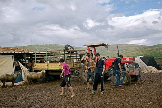 Mashid Mohadjerin's spontaneous shot: teenagers mill around a tractor and trailer in a muddy field, one of them smoking.