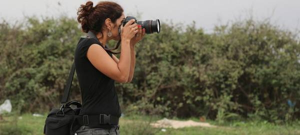 Mashid Mohadjerin holds a Canon camera to her eye as she takes a photograph.