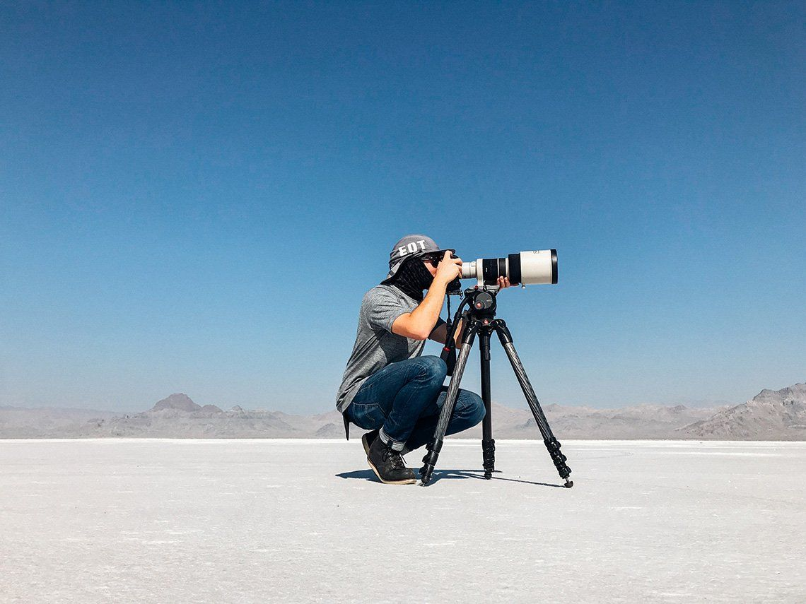 Photographing a cycling world record: Matt Ben Stone crouches behind his Canon camera and lens on a tripod in Utah salt flats.