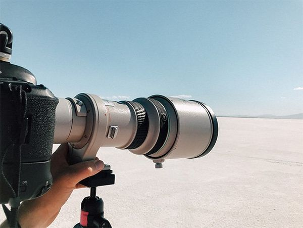A long Canon lens is pointed out at Utah's salt flats.