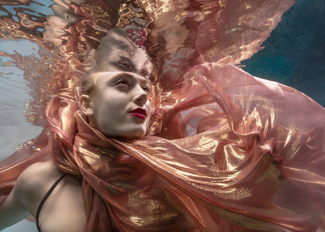 A woman submerged in water with a pink and gold scarf billowing around her.