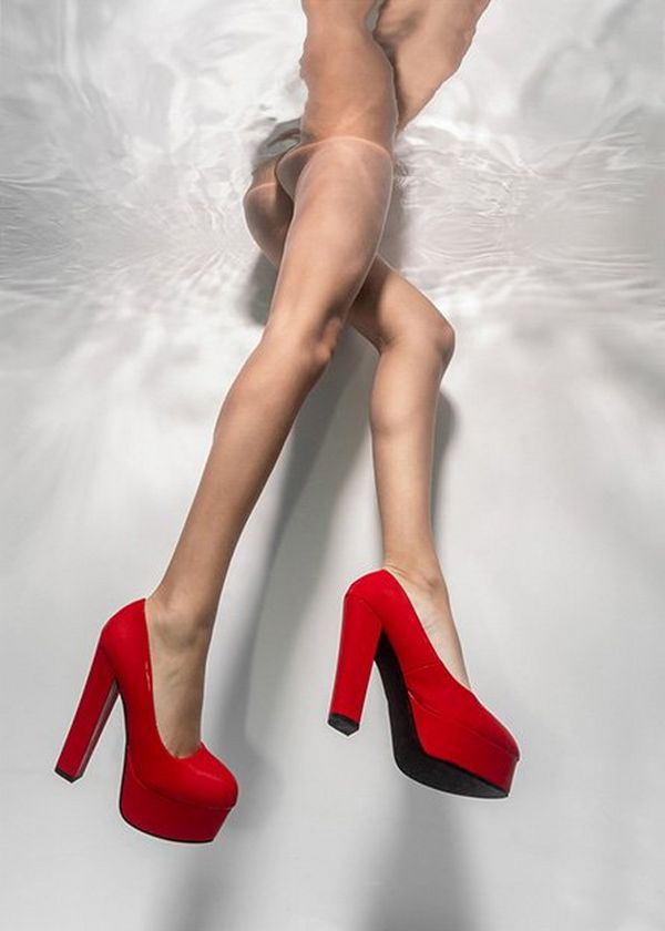 Underwater shot of a pair of legs with chunky red high-heeled shoes on.