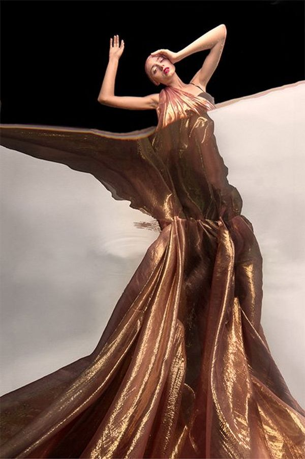 A woman draped in gold fabric, with half her body seen from underwater.