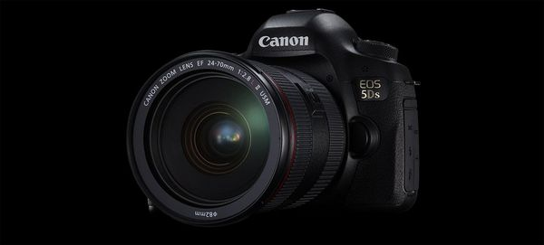 A Canon EOS 5DS DSLR with a zoom lens is seen against a black background.