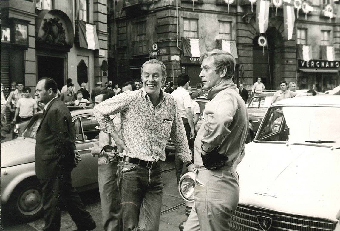 Michael Deeley and Michael Caine leaning on minis in Italy.