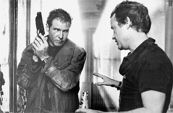 Harrison Ford dressed as Rick Deckard on the set of Blade Runner, talking to director Ridley Scott