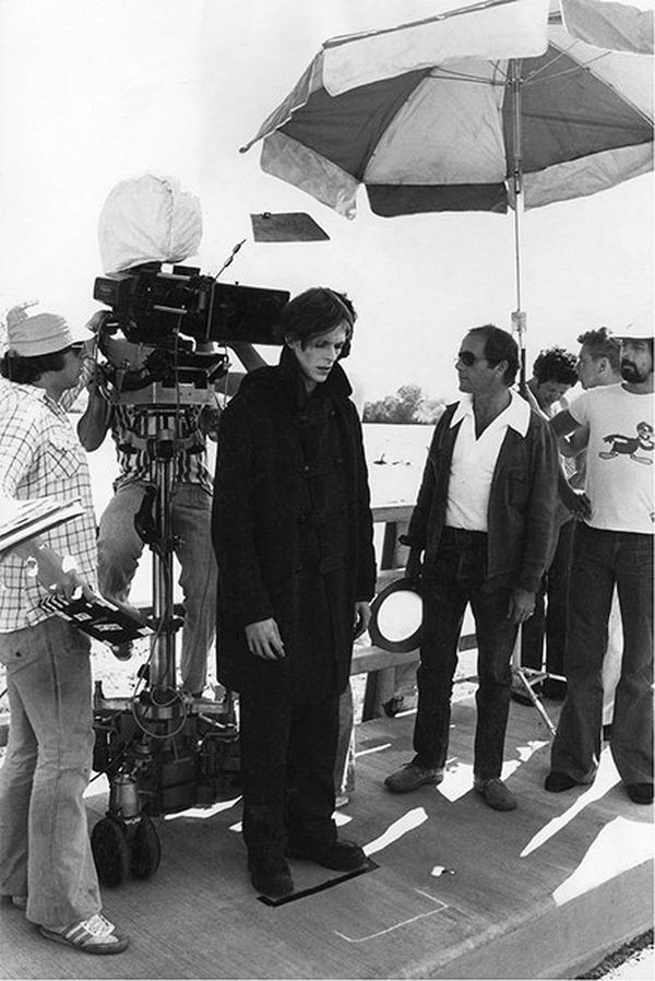 David Bowie in costume as Thomas Jerome Newton on the set of The Man Who Fell to Earth, surrounded by the film crew.