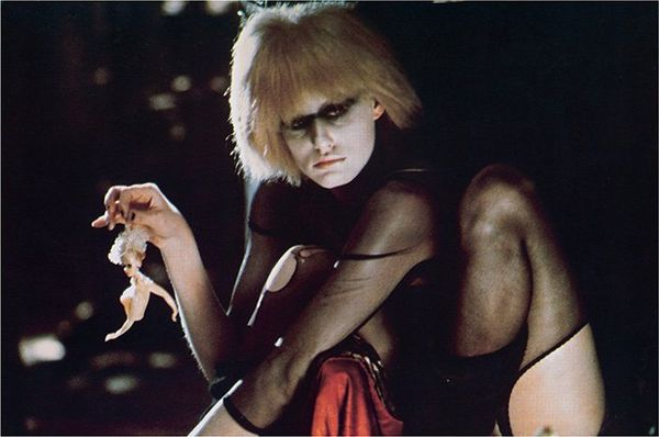 Daryl Hannah in costume as Pris from Blade Runner, wearing a sheer black leotard, heavy black eye makeup and holding a doll by the hair.