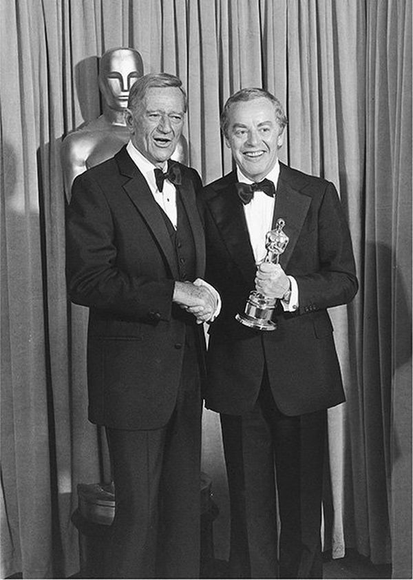 John Wayne and Michael Deeley shaking hands at the Oscars, Michael holding an award.