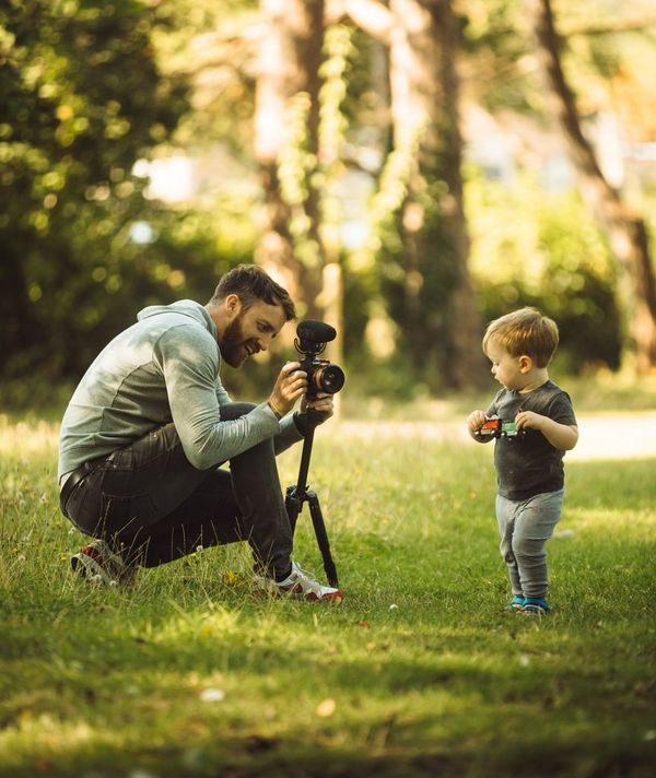 Stefan Michalak filming a toddler in the park.