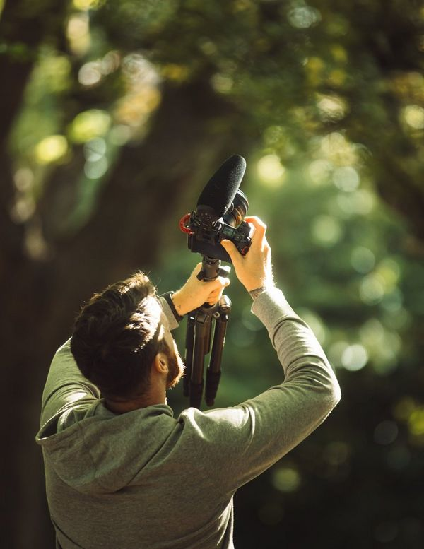 Stefan Michalak holding his kit up to film the trees in the park.