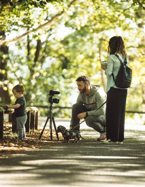 The Michalaks filming on a path in the park with their dog.
