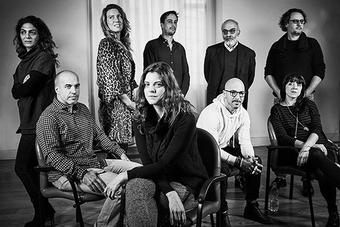 Nine men and women stand or sit in a group, in a room set up with photographers' light stands. The black and white photo shows Mashid Mohadjerin, Ilvy Njiokiktjien, Daniel Etter, Roberto Koch, Paolo Pellegrin, Alvaro Ybarra Zavala, Carolina Arantes, Magnus Wennman, Simona Ghizzoni.