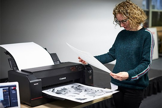 Helen Bartlett stands next to a Canon imagePROGRAF PRO-1000 printer looking at an A2 black and white photo print.