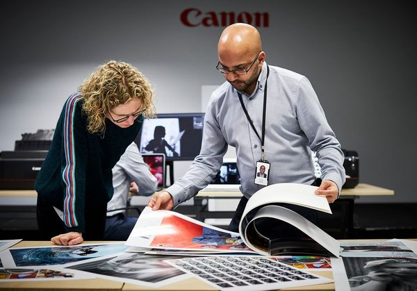 Helen Bartlett with Canon Inkjet Specialist Suhaib Hussain looking through an A2 book of prints.
