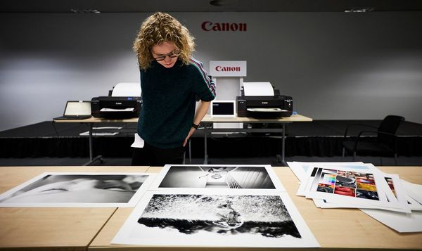 Helen Bartlett inspecting her A2 prints laid out on a table.