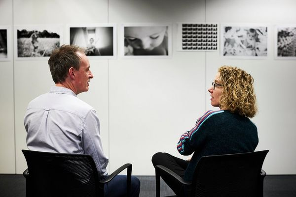 Jay Sinclair and Helen Bartlett sit discussing a set of prints of Helen's photographs displayed on a wall.