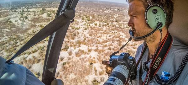Neil Aldridge in a light aircraft looking out over the African grasslands below, holding a Canon EOS 5D camera.