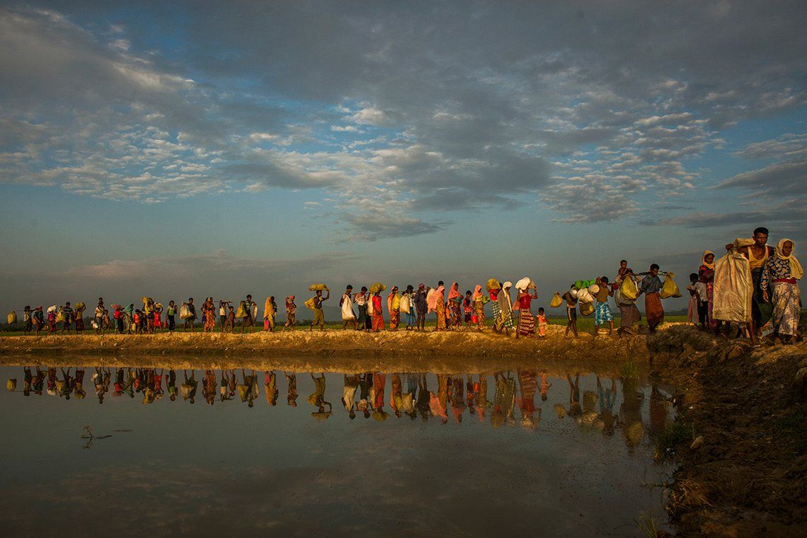 A line of Rohingya Muslim people carry bags of possessions. Photo by Salahuddin Ahmed on a Canon EOS 5D Mark II.