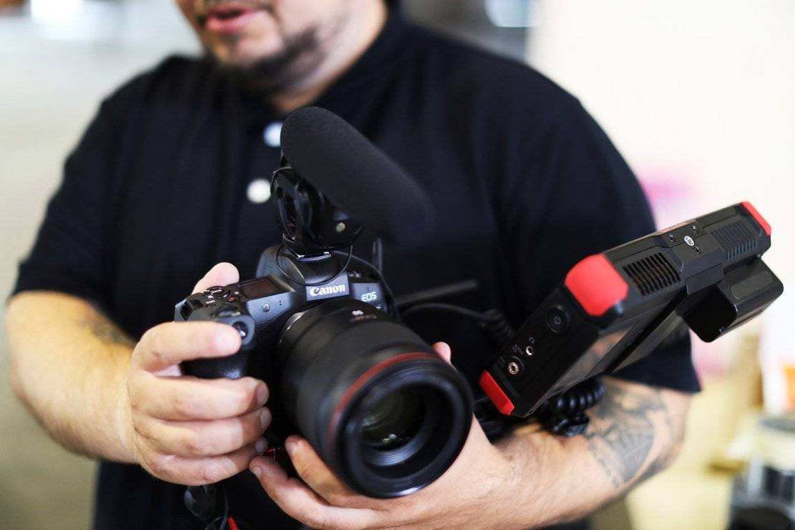 Filmmaker Nicolai Brix, seen out-of-focus from the chin down, holds a Canon EOS R with a microphone attached to the flash shoe at its top and an external display mounted at the side.