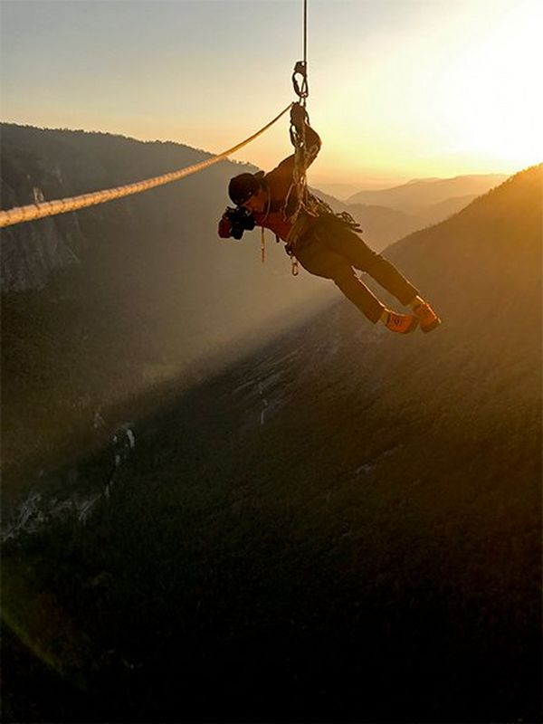 Cinematographer Jimmy Chin dangles in mid air as he films, with the hills of Yosemite National Park lit by the sunset behind him.