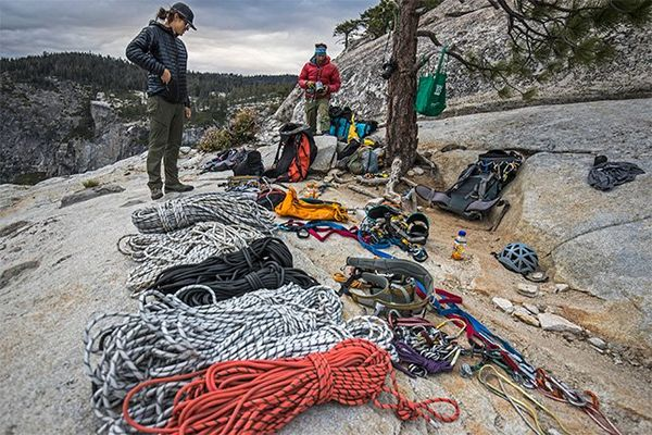 Ropes and climbing equipment laid out over a rocky clearing as two of the crew pack up after filming.
