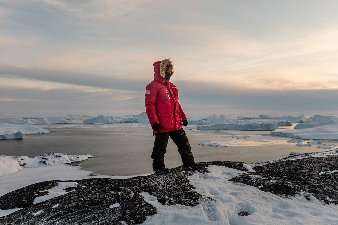 An Ariston installer wearing a red puffer jacket with a fur-effect hood, balaclava and eye protection stands on snow-covered rocks in front of a body of water strewn with icebergs.