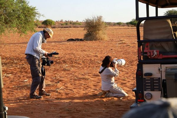 Alex Wykes films Marina Cano as she kneels in the desert sand and shoots with a Canon EOS-1D X Mark III.