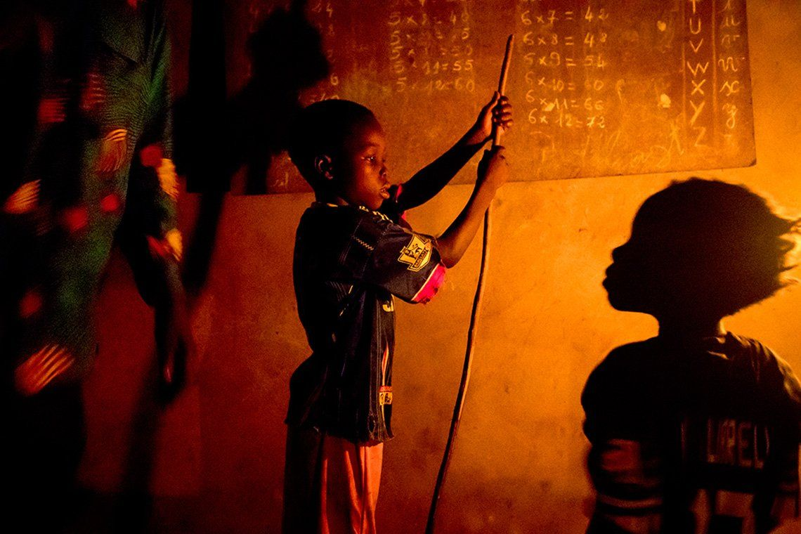 Two children stand in front of a blackboard at home in the village of Allankpon, Benin, practicing multiplication tables thanks to the orange light of a kerosene lamp.