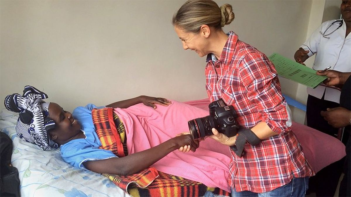 Photographer Georgina Goodwin, holding her Canon camera, greets a woman in a hospital bed in Kenya.