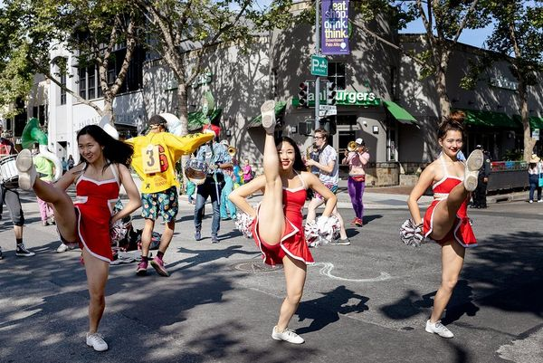 Three cheerleaders do high kicks in the middle of a street. Photo by Laura Morton.