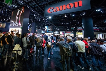 In the Canon area at photokina, visitors walk down an area lined with gallery images, a Canon logo above them.