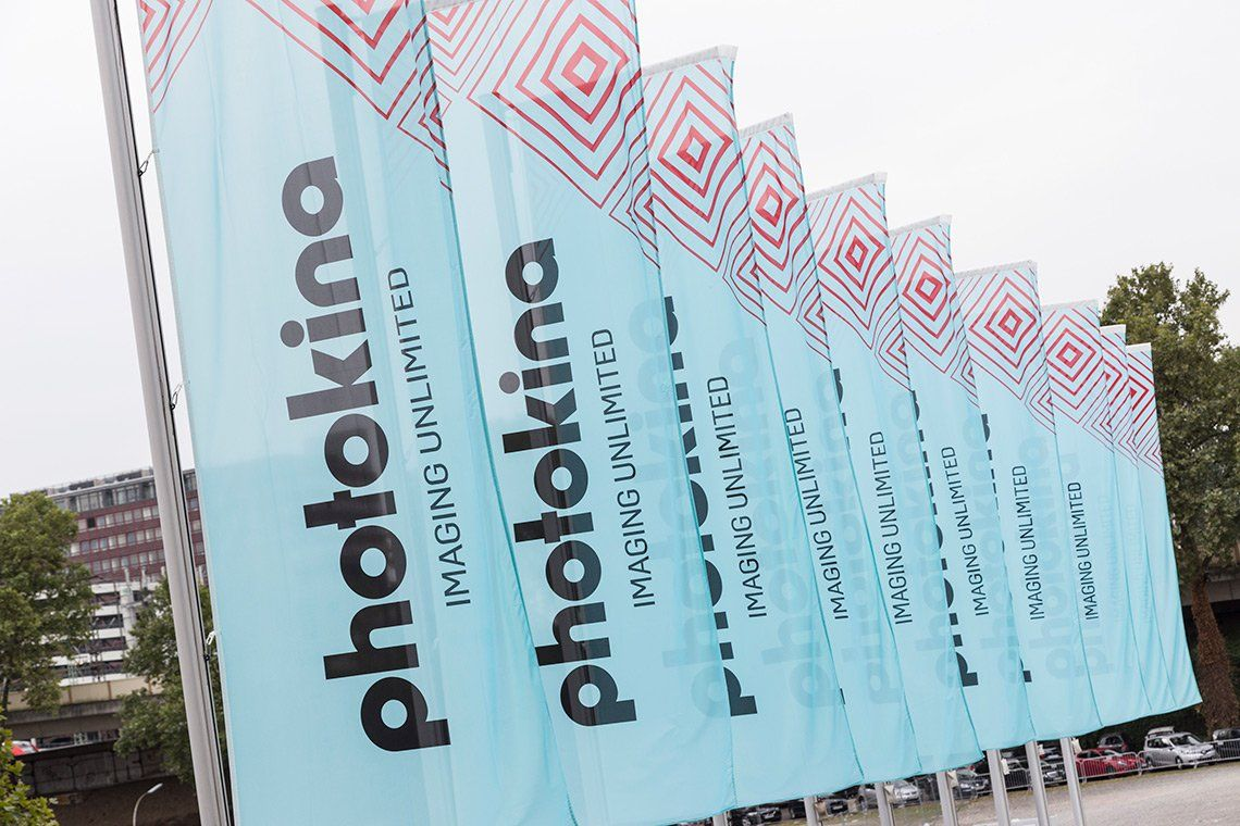 A row of light blue flags at the entrance to the Photokina trade show.