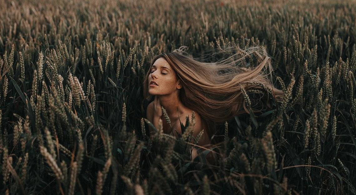 Rosie Hardy closes her eyes as she stands in a field of wheat as tall as her. Portrait by Rosie Hardy on a Canon EOS 5D Mark II.