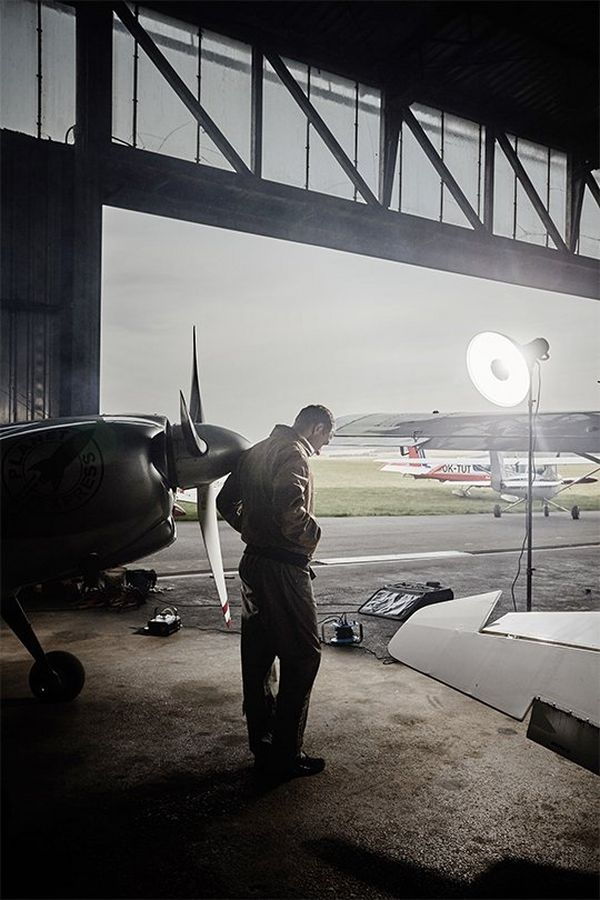 Martin Šonka stands in an aircraft hangar beside a small plane. Portrait by David Turecký on a Canon EOS 6D.