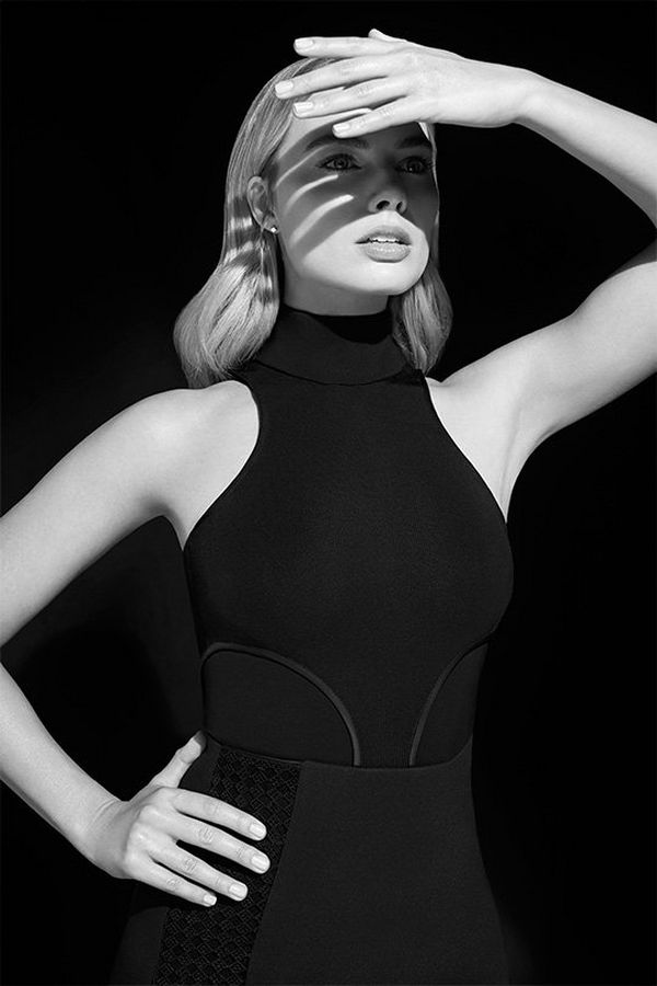 A black and white portrait of Margot Robbie holding up a hand to shield her eyes from the sun. Portrait by Lorenzo Agius.