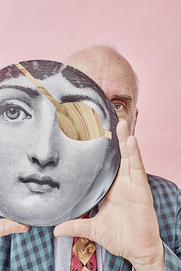 Designer Barnaba Fornasetti holds a mask with a single, large eye hole in front of his face. Colourful portrait by David Turecký on a Canon EOS 6D.